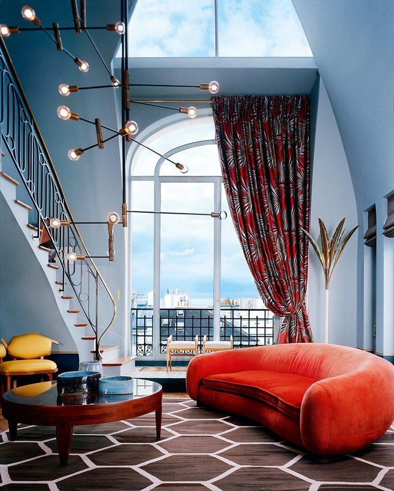 Chic Parisian LR with orange sofa and print draperies