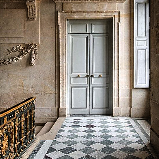 Formal French hallway with marble floor, limestone wall and bronze railing